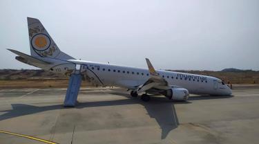 Penampakan pesawat Myanmar National Airline (MNA) yang mendarat tanpa roda depan di Bandara Internasional Mandalay, Myanmar, Minggu 12 Mei 2019. Pesawat dengan nomor penerbangan UB-103 dan bertipe Emraer-190 itu mengangkut 82 penumpang serta tujuh kru. (Aung Thura via AP)