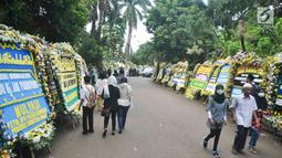 Warga berjalan di sekitar tempat persemayaman Ani Yudhoyono di Puri Cikeas, Bogor, Jawa Barat, Minggu (2/6/2019). Ani Yudhoyono akan dimakamkan di TMP Kalibata pada pukul 15.00 WIB.(Liputan6.com/Immanuel Antonius)