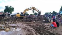 Warga menyaksikan ekskavator membersihkan puing pada daerah yang terkena banjir bandang di Waiwerang, Pulau Adonara, Nusa Tenggara Timur, Selasa (6/4/2021). Tim penyelamat terus menggali puing tanah longsor untuk mencari korban yang terkubur usai bencana banjir bandang. (AP Photo/Rofinus Monteiro)