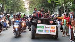 Pengisi acara Karnaval SCTV menyapa warga saat mengikuti pawai artis keliling Kota Bojonegoro, Jawa Timur, Sabtu (30/3). Karnaval SCTV di Bojonegoro berlangsung pada 30-31 Maret 2019. (Liputan6.com/Pool/SCTV)