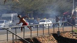 Seorang penduduk asli Brasil melempari polisi dengan batu saat demo menentang RUU Reformasi Agraria di luar Kongres di Brasilia, Brasil, Selasa (22/6/2021). Penduduk asli Brasil menilai RUU Reformasi Agraria akan membatasi pengakuan lahan reservasi. (AP Photo/Eraldo Peres)