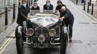 Staf mendorong Bugatti Type 57S 1937, salah satu mobil pra-perang paling diinginkan di dunia, di luar rumah lelang Bonhams,  London, Selasa (16/2/2021). Bugatti ini telah tersembunyi selama 50 tahun terakhir dan merupakan salah satu dari 42 contoh varian 57S yang diproduksi (AP Photo/Frank Augstein)