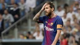 Striker Barcelona, Lionel Messi, memegang kepalanya usai takluk dari Real Madrid pada laga Piala Super Spanyol 2017 di Stadion Santiago Bernabeu, Rabu (16/8/2017). Real Madrid menang 2-0 atas Barcelona. (AFP/Curto De La Torre)
