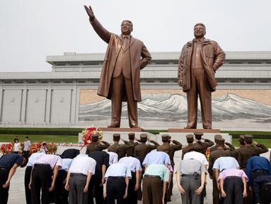 Tentara memberi hormat ketika yang lain membungkuk di hadapan patung pemimpin Korea Utara Kim Il Sung dan Kim Jong Il dalam peringatan berakhirnya Perang Dunia II dan pembebasan dari kolonial Jepang di Pyongyang, Korut, Rabu (15/8). (AP Photo/Ng Han Guan)