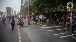 Petugas Satpol PP berjaga saat warga berolahraga pada car free day (CFD) di kawasan Bundaran HI, Jakarta, Minggu (17/11/2019). Usai ditertibkan, tak terlihat satu pun PKL yang berjualan di lokasi tersebut. (Liputan6.com/Faizal Fanani)