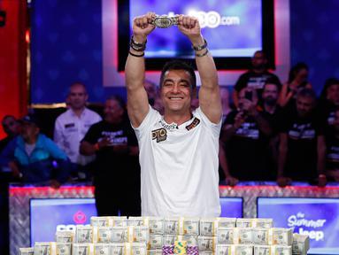 Pemain poker Hossein Ensan berpose dengan tumpukan uang sambil menunjukkan sebuah gelang usai memenangkan World Series of Poker di Las Vegas, Amerika Serikat, Rabu (17/7/2019). Pria asal Jerman tersebut mengalahkan pemain poker asal Italia, Dario Sammartino. (AP Photo/John Locher)