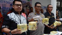 Kabid Humas Polda Metro Jaya Kombes Pol Argo Yuwono (tengah) menunjukkan barang bukti kasus narkoba di Polda Metro Jaya, Jakarta, Jumat (1/3). Subdit II Resnarkoba menangkap lima tersangka dalam kasus ini. (Merdeka.com/ImamBuhori)