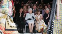 Ratu Elizabeth II duduk di sebelah Anna Wintour dan chief executive British Fashion Council, Caroline Rush menyaksikan London Fashion Week 2018, Selasa (20/2). Ratu Elizabeth datang di hari terakhir London Fashion Week. (Yui Mok/Pool photo via AP)