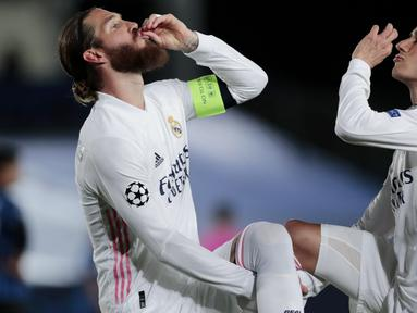 Pemain Real Madrid, Sergio Ramos, melakukan selebrasi bersama Lucas Vazquez usai mencetak gol ke gawang Atalanta pada laga Liga Champions di Stadion Alfredo di Stefano, Rabu (17/3/2021). Real Madrid menang dengan skor 3-1. (AP/Bernat Armangue)