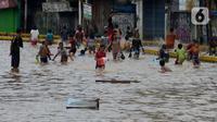 Anak-anak bermain air saat banjir menggenangi Jalan Jatinegara Barat, Jakarta, Kamis (2/1/2020). Hujan yang terjadi kemarin malam membuat Kali Ciliwung meluap ke jalan. (merdeka.com/Imam Buhori)