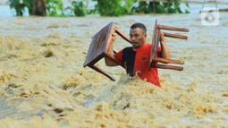 Warga membawa barang miliknya saat banjir bandang  di Kabupaten Bone Bolango, Gorontalo (11/6/2020). Data sementara yang diterima dari BPBD Kabupaten Bone Bolango sekitar 1.078 kepala keluarga serta 5.407 jiwa terdampak banjir bandang. (Liputan.com/Arfandi Ibrahim)