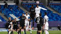Bek Real Madrid, Raphael Varane (kanan) berusaha menyundul bola saat bertanding melawan Borussia Monchengladbach pada Grup B Liga Champions di Estadio Alfredo Di Stefano, Kamis (10/12/2020). Kemenangan ini mengantar Madrid lolos ke babak 16 besar Liga Champions. (AFP/PIERRE-PHILIPPE MARCOU)