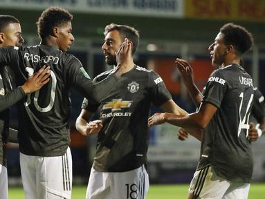 Para pemain Manchester United merayakan gol yang dicetak oleh Marcus Rashford ke gawang Luton Town pada Piala Liga Inggris di Stadion Kenilworth Road, Rabu (23/9/2020). Setan Merah menang dengan skor 3-0. (Nick Potts/Pool via AP)