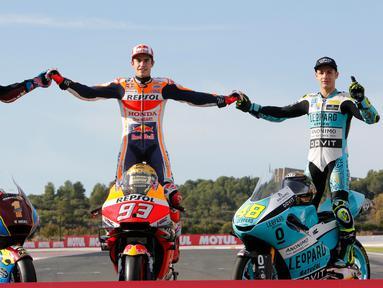 Pembalap MotoGP Marc Marquez (tengah) bersama pembalap Moto2 Alex Marquez (kiri) dan pembalap Moto3 Lorenzo Dalla Porta (kanan) berpose di depan Valencia Motorcycle Grand Prix, Spanyol, Minggu (17/11/2019). Ketiganya sukses merebut gelar juara dunia tahun 2019. (AP Photo/Alberto Saiz)