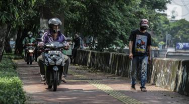 Sejumlah pengendara motor melintas di atas trotoar pejalan kaki di kawasaan Daan Mogot, Jakarta, Senin (26/4/2021). Padatnya volume kendaraan pada jam kerja di kawasan itu membuat sejumlah pengendara motor nekat menggunakan trotoar yang merupakan hak bagi pejalan kaki. (Liputan6.com/Faizal Fanani)