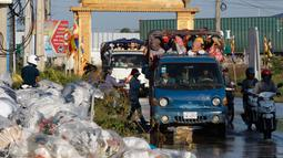 Dua mobil bak terbuka mengangkut para pekerja pulang ke rumah dari tempat kerja di sebuah pabrik di dekat desa Trapang Anchanh, di luar Phnom Penh, Kamboja (27/10). (AP Photo/Heng Sinith)