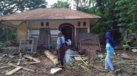 Para wanita berjalan melewati rumah yang rusak akibat banjir bandang di Waiwerang, Pulau Adonara, Nusa Tenggara Timur, Selasa (6/4/2021). Tim penyelamat terus menggali puing tanah longsor untuk mencari korban yang terkubur usai bencana banjir bandang. (AP Photo/Rofinus Monteiro)