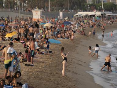 Seorang wanita mengambil foto saat menikmati cuaca panas di pantai di Barcelona, Spanyol, Kamis (12/8/2021). Layanan cuaca nasional Spanyol memperingatkan suhu bisa mencapai 44 derajat Celcius (111 derajat Fahrenheit) di beberapa daerah dalam beberapa hari mendatang. (AP Photo/Joan Mateu Parra)