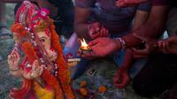 Umat Hindu India berdoa sebelum membenamkan patung Dewa Ganesha di kolam sementara dekat sungai Gangga, Allahabad, India, Selasa (5/9). Patung berkepala gajah ini merupakan anak dari Dewa Shiva dan Dewi Parvati. (Rajesh Kumar Singh/AP)