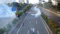 Massa menghindari gas air mata saat bentrok dengan polisi di jalan tol dalam kota di kawasan Slipi, Jakarta, Rabu (22/5/2019). Jalan tol  dalam kota sempat ditutup sekitar setengah jam, dan massa dihalau petugas ke arah kemanggisan. (merdeka.com/Arie Basuki)