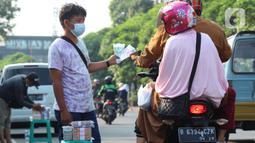 Penjual jasa penukaran uang baru menawarkan uang baru kepada pengguna Jalan Otista Raya di Karawaci, Kota Tangerang, Senin (10/5/2021). Penjual jasa penukaran uang baru musiman tersebut mulai bermunculan menjelang lebaran yang dikenakan tarif jasa sebesar 10 persen. (Liputan6.com/Angga Yuniar)