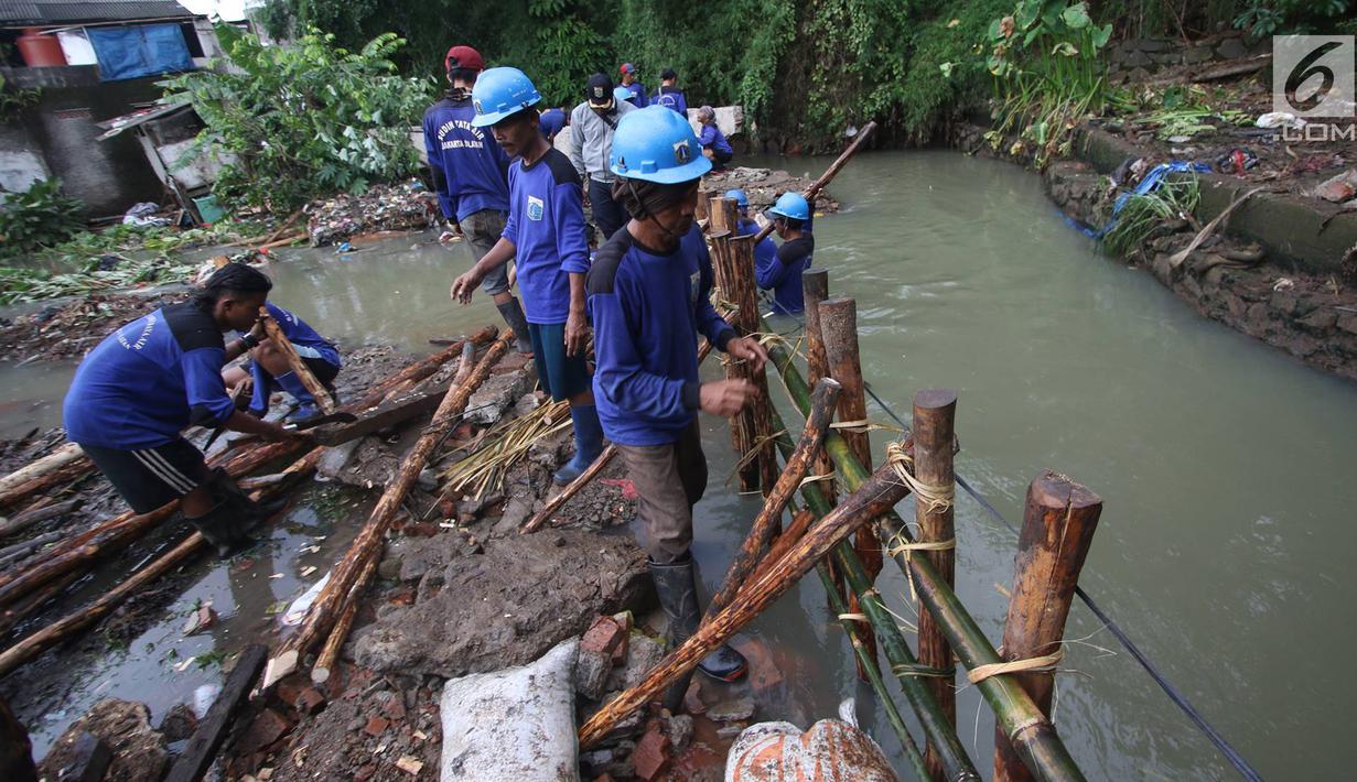 Pekerja menyelesaikan pembuatan tanggul darurat di kawasan Jatipadang, Jakarta, Rabu (22/11). Jebolnya tanggul Kali Pulo di kawasan tersebut menyebabkan puluhan rumah terendam banjir. (Liputan6.com/Immanuel Antonius)