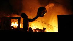 Seorang pria berusaha menyiramkan air saat kebakaran di lingkungan Educandos, di Manaus, Brasil (17/12). Kebakaran diduga disebabkan oleh ledakan panci presto yang menghanguskan ratusan rumah warga. (AP Photo/Edmar Barros)