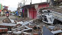Pengendara sepeda motor melewati mobil yang terkubur puing reruntuhan bangunan akibat gempa di Mamuju, Sulawesi Barat, Indonesia, Senin (18/1/2021). Sebanyak 253 warga mengalami luka berat akibat gempa di Kabupaten Majene dan Mamuju. (AP Photo/Yusuf Wahil)