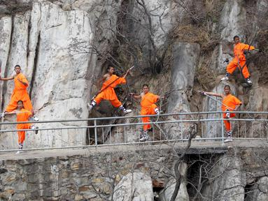 Sejumlah murid kungfu shaolin melakukan gerakan berbahaya diatas tebing gunung  Songshan, , China , (17/3). Dengan berpakaian kungfu dan senjata lengkap mereka berlatih dengan kompak. (REUTERS / China Daily)