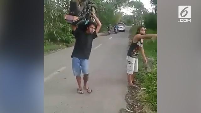 Bukannya memanggil jasa derek ketika mengalami ban bocor, pria ini malah menggendong motornya ke bengkel. Begini aksinya!