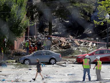 Pemadam kebakaran mengamati puing bangunan apartemen di Sivler Spring, Maryland, Washington DC, Kamis (11/8). Sedikitnya 2 orang tewas dan tujuh lainnya hilang setelah ledakan gas alam yang menyebabkan kebakaran di apartemen itu. (REUTERS/Joshua Roberts)