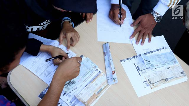 Warga mengisi formulir untuk membayar pajak kendaraan bermotor di samsat keliling di car free day, Jakarta, Minggu (27/8). Perpanjangan STNK tanpa BPKB hanya berlaku di gerai Samsat Keliling car free day. (Liputan6.com/Angga Yuniar)
