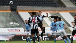 Bek Newcastle United, Emil Krafth (tengah) melepaskan sundulan yang berbuah gol pertama timnya ke gawang Manchester City dalam laga lanjutan Liga Inggris 2020/2021 pekan ke-36 di St James' Park, Newcastle, Jumat (14/5/2021). Newcastle kalah 3-4 dari Manchester City. (AFP/Scott Heppell/Pool)