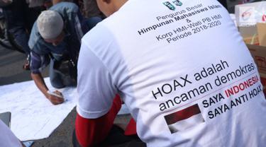 Salah satu pengurus PB HMI melihat warga yang menandatangani spanduk dukungan anti hoax di kawasan Bundaran Hotel Indonesia, Jakarta, Minggu (18/11). PB HMI mensosialisasikan Hoax sebagai ancaman demokrasi di Indonesia. (Liputan6.com/Helmi Fithriansyah)