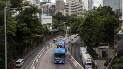 Sebuah bus atap terbuka membawa anggota delegasi Olimpiade Hong Kong selama parade, setelah Olimpiade Tokyo 2020, di Hong Kong, Kamis (19/8/2021). Hong Kong yang memiliki 46 atlet perwakilan pada Olimpiade Tokyo 2020 berhasil mengumpulkan satu emas, dua perak dan tiga perunggu. (ISAAC LAWRENCE/AFP)
