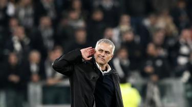 Manajer Manchester United, Jose Mourinho berselebrasi dengan meletakkan tangan di telinganya ke arah para pendukung Juventus pada akhir Matchday 4 Grup H Liga Champions di Allianz Stadium, Rabu (7/11). MU mengalahkan Juventus 1-2. (Marco BERTORELLO/AFP)