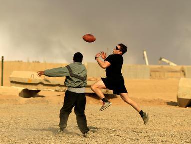 Tentara AS berusaha menangkap bola saat bermain American Football pada Thanksgiving di dalam pangkalan militer AS di Qayyara, selatan Mosul, Irak (24/141). (REUTERS/Thaier Al-Sudani)