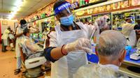 Para barber memangkas rambut pelanggan di sebuah tempat pangkas rambut di Kuala Lumpur, Juni 2020. Setelah hampir tiga bulan masa lockdown, pemerintah Malaysia melakukan pelonggaran sebagai upaya menghidupkan kembali perekonomian yang sempat terpukul akibat pandemi Covid-19. (Xinhua/Zhu Wei)