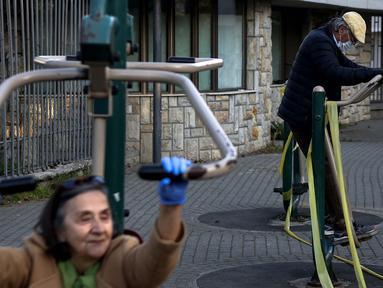 Dua lansia tengah berolahraga di sebuah taman di Beograd, Serbia (21/4/2020). Setelah hampir sebulan 'dikurung' sebagai upaya mencegah penularan Covid-19, orang-orang berusia 65 tahun atau lebih kini diizinkan keluar rumah oleh pemerintah Serbia. (AFP/Oliver Bunic)