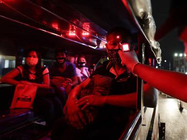 Polisi memeriksa suhu tubuh penumpang dalam jeepney di pos pemeriksaan virus corona COVID-19 di Manila, Filipina, Senin (16/3/2020). Polisi beserta petugas lalu lintas dan petugas desa melakukan pengecekan suhu tubuh warga untuk mencegah penyebaran virus corona COVID-19. (AP Photo/Aaron Favila)
