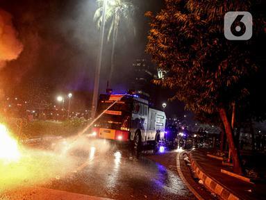 Mobil polisi menyemprotkan air untuk memadamkan api usai demonstrasi yang berujung anarkis di kawasan Bundaran HI, Jakarta, Kamis (8/10/2020). Massa membakar sejumlah barang saat demonstrasi menolak pengesahan UU Cipta Kerja. (Liputan6.com/Faizal Fanani)