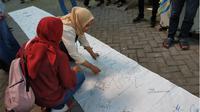 Wali murid membubuhkan tanda tangan tolak PPDB sistem zonasi di Kantor Dispendik Surabaya. Foto: Abidin suarasurabaya.net