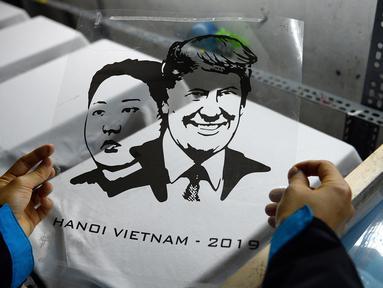 Seorang pekerja Vietnam bersiap untuk mencetak kaus bergambar wajah Presiden AS Donald Trump dan pemimpin Korea Utara Kim Jong-un di Hanoi, Jumat (22/2). Pembuatan kaus itu menyambut KTT kedua AS-Korea Utara pada 27 Februari mendatang. (Nhac NGUYEN/AFP)