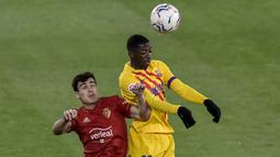 Bek Osasuna, Manu Sanchez (kiri) berduel udara dengan striker Barcelona, Ousmane Dembele dalam laga lanjutan Liga Spanyol 2020/21 pekan ke-26 di El Sadar Stadium, Pamplona, Sabtu (6/3/2021). Osasuna kalah 0-2 dari Barcelona. (AP/Alvaro Barrientos)