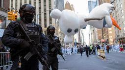 Polisi bersenjata lengkap berjaga ketika balon Olaf melayang di atas kawasan Sixth Avenue selama Parade Macy's Thanksgiving Day di New York, Kamis (22/11). Membelah jalanan kota, Parade Macy's selalu ditunggu setiap tahunnya. (AP/Mary Altaffer)