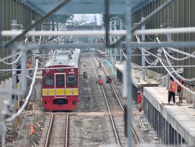 KRL Commuter Line Jabotabek melintas di dekat proyek pembangunan Kereta Api Bandara Soekarno-Hatta di Kawasan Dukuh Atas, Jakarta, Selasa (28/2). (Liputan6.com/Yoppy Renato)