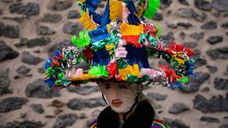 Seorang peserta mengenakan pakaian tradisional dan topi yang dikenal sebagai '' Ttutturo '' berpose di sela acara karnaval di desa Pyrenees Leitza, Spanyol (30/1). (AP Photo / Alvaro Barrientos)