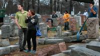 Sally Amon dan anaknya Max Amon saat melihat batu nisan neneknya yang dirusak usai mendapatkan serangan vandalisme di Chesed Shel Emeth Cemetery di University City, St Louis, Missouri, (21/2). (Robert Cohen /St. Louis Post-Dispatch via AP)