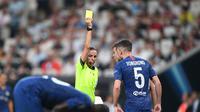 Wasit wanita Stephanie Frappart memberikan kartu kuning kepada pemain Chelsea, di laga UEFA Super Cup: Liverpool vs Chelsea, Rabu (14/8). (Bulent Kilic / AFP)
