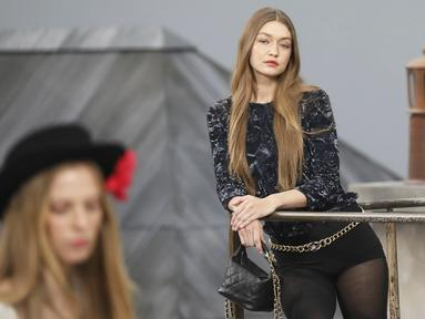 Model Gigi Hadid berpose saat mengenakan busana koleksi desainer Virginie Viard dalam Paris Fashion Week, di Prancis (1/10/2019). Gigi Hadid membawakan koleksi women's ready-to-wear 2020 dari rumah mode Chanel. (AP Photo/Vianney Le Caer)